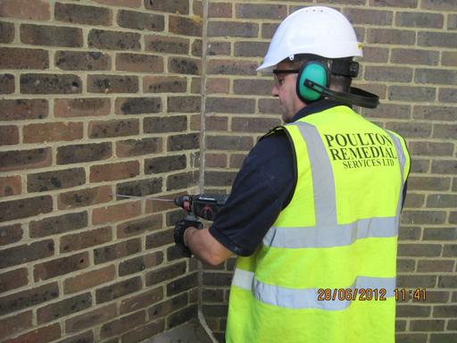 Poulton Remedial worker wearing Hi-Viz vest, hardhat and hearing protectors whilst drilling into a wall
