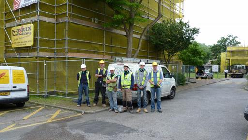 Poulton Remedial team in Hi-Viz vests and hardhats in-front of scaffolding highlighting their commitment to safety